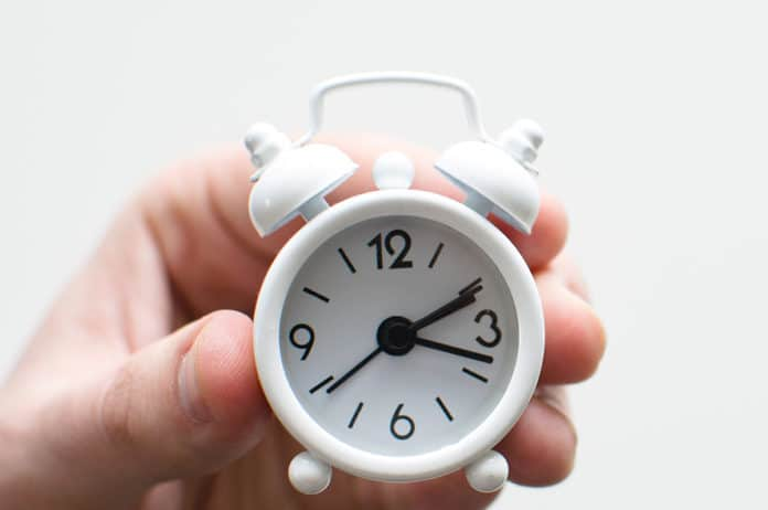 A hand holds a tiny white alarm clock