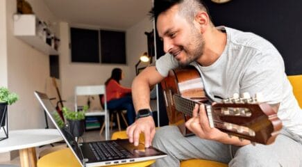man-playing-guitar-in-front-of-computer